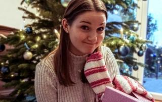 Frau mit falschem Lächeln vor einem Weihnachtsbaum mit Weihnachtsgeschenk zum Umtauschen in der Hand.
