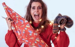Panische Frau mit Geschenkpapier und Socken in den Händen.