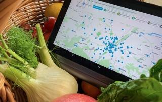 """Geöffnete Webseite """"München bringt's"""" auf Tablet, welches in Obstkorb liegt."""