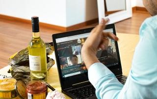 Person sitzt gemütlich mit Snacks und Getränken am Computer und führt ein aktives Gespräch per Videochat.