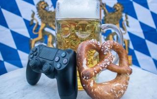Ein Game-Controller und eine Breze sind an einen Maßkrug angelehnt. Im Hintergrund befindet sich die Bayerische Fahne.