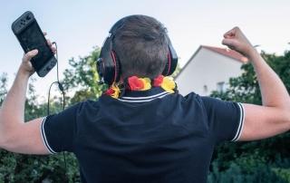 Eine Mann freut sich über seinen Sieg. Dabei trägt er eine deutsche Blumenkette, Spielekonsole und Kopfhörer, um die Games-Branche zu symbolisieren.