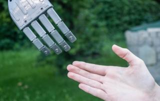 Ein Roboter gibt einem Menschen die Hand. Kann KI oder Roboter in naher Zukunft in der Pflege aushelfen?