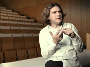 Professor Dirk Labudde von der Hochschule Mittweida vor einem leeren Vorlesungssaal. Er spricht und erklärt dabei etwas mit den Händen.
