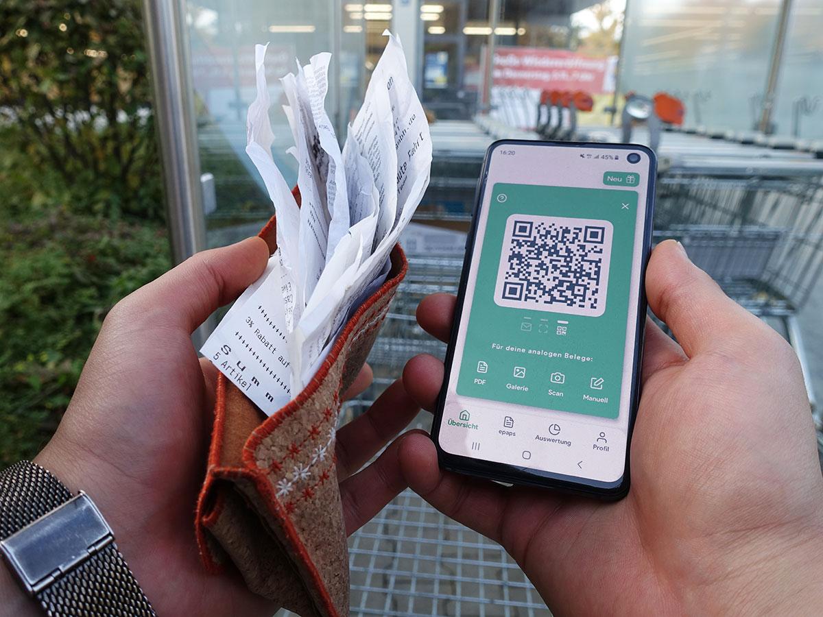 Smartphone mit QR-Code und Kassenbelege.