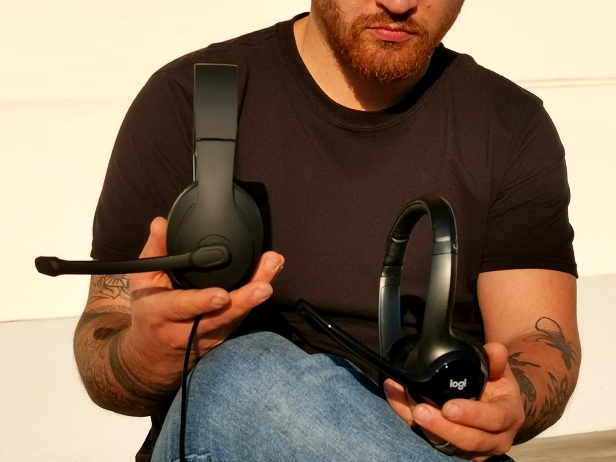 Mann hält in beiden Händen Headsets die im Vergleich stehen