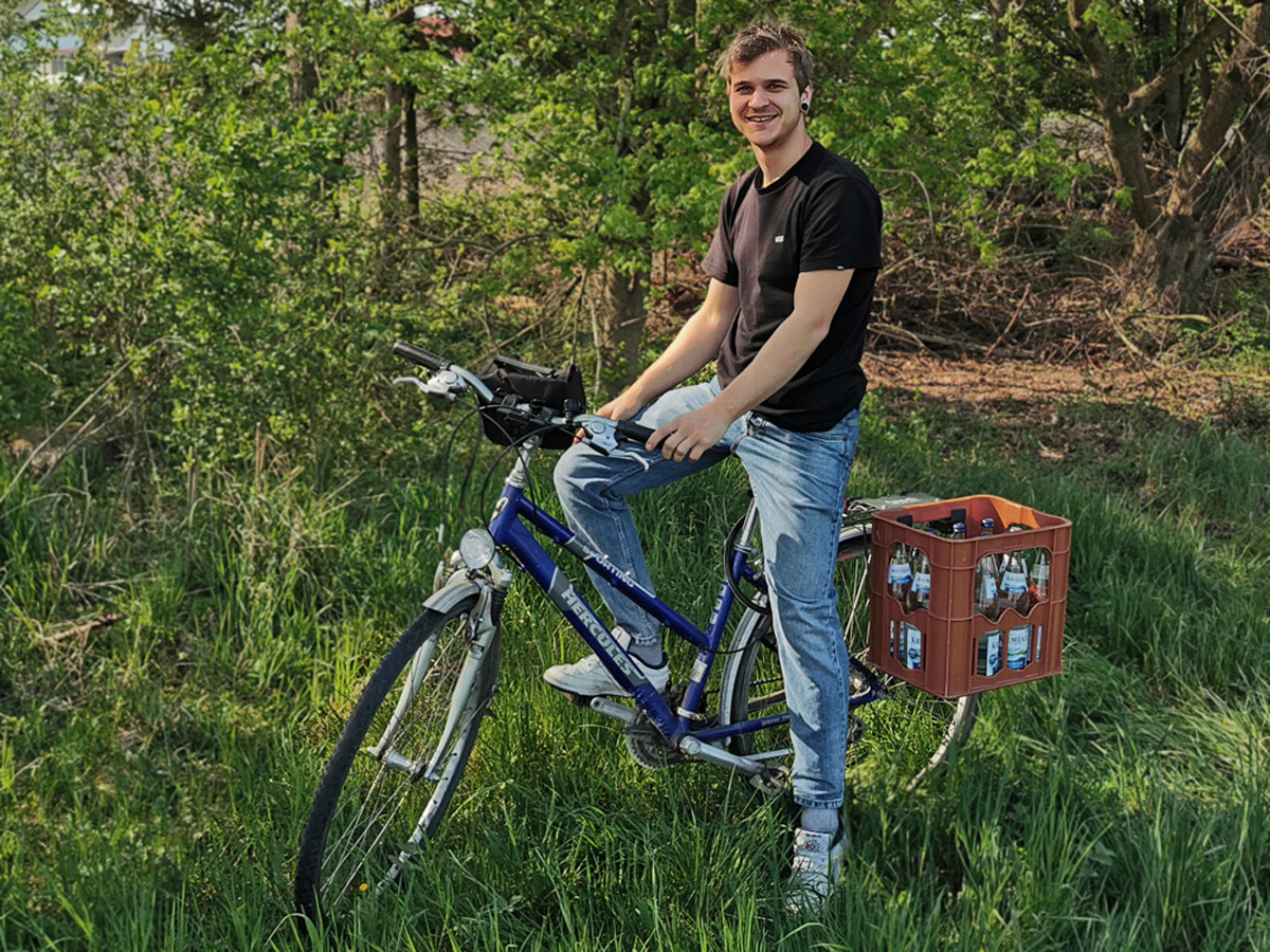 Der Start-Up Gründer sitzt auf seinem Fahrrad, auf dem Gepäckträger transportiert er eine Getränkekiste mit der Kistenhalterung.