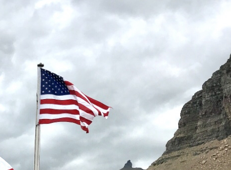 The American and Canadian flags are flying in the wind at the top of two flags poles. In the background are mountain ranges and trees.