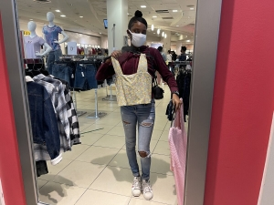 Girl at a shopping mall trying on different blouses in front of the mirror.